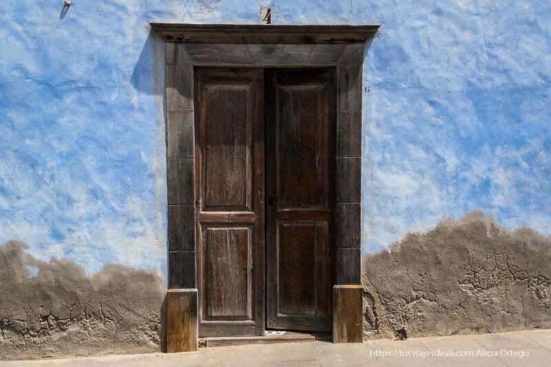 puerta de madera marrón oscuro con dintel y alrededor muro de color añil