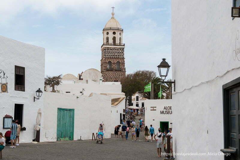 torre de la iglesia sobresaliendo entre casas bajas blancas y calle con bastante gente
