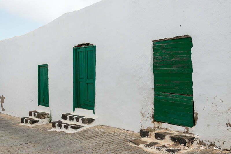 tres puertas verdes con dos escalones de lava en un muro blanco en teguise