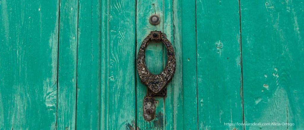 puerta pintada de verde con aldabón de hierro y mirilla en Teguise