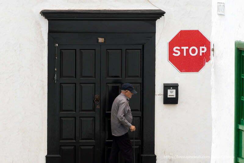 anciano andando con bastón frente a puerta de madera pintada de negro y señal de stop a la derecha