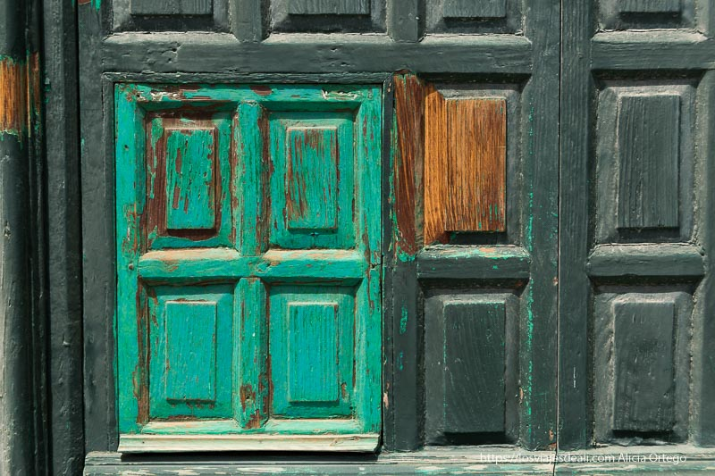 cuarterones de una puerta pintados de verde oscuro y turquesa