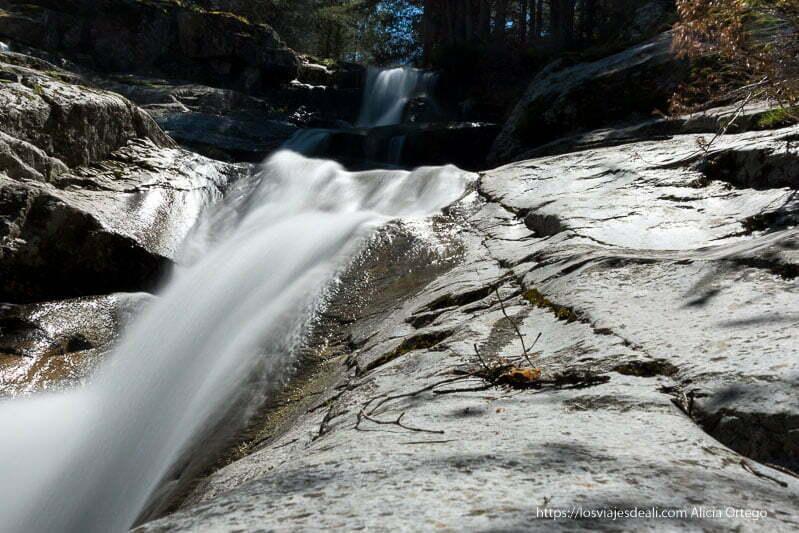 cascada con agua como si fuera seda entre grandes rocas de granito cerca del puerto de navafría