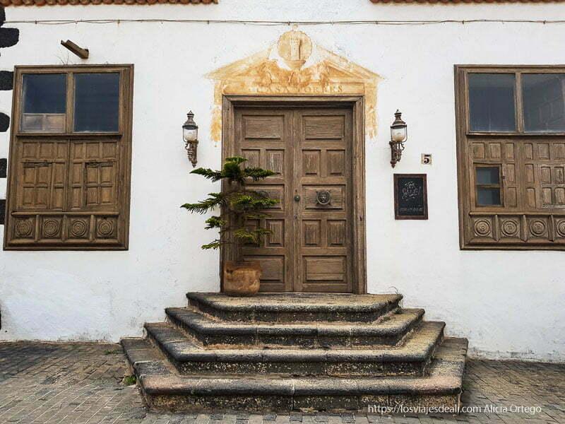 puerta principal de un antiguo palacio con cuatro escalones de piedra y ventanas de madera a los lados