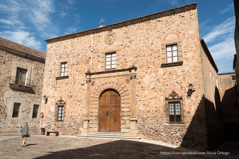 palacio de piedra con gran puerta en forma de arco y ventanas con celosías de hierro