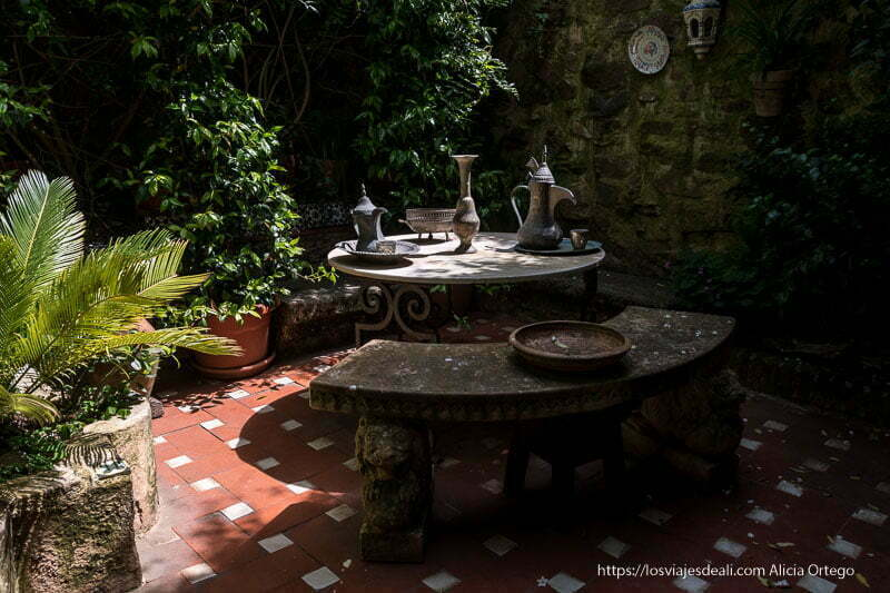 patio de la casa museo árabe con muchas plantas y mesita con antiguas cafeteras árabes