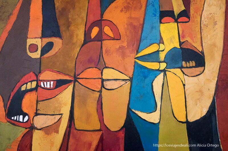 detalle de un cuadro de guayasamin varios rostros a la altura de la nariz y boca en colores vivos