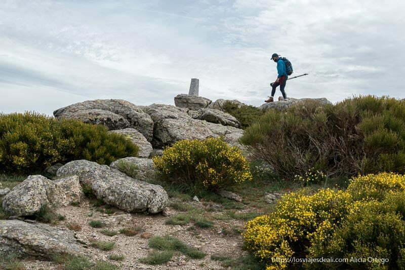 excursionista llegando a una pequeña cumbre con un hito de piedra
