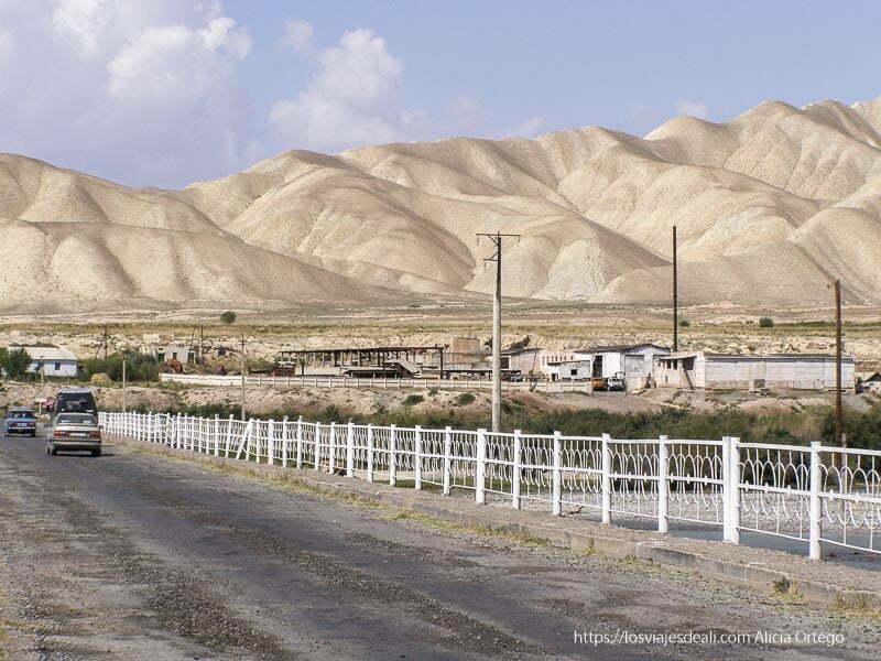 carretera con algunas casas y grandes montañas peladas de color marrón en la ruta de la seda