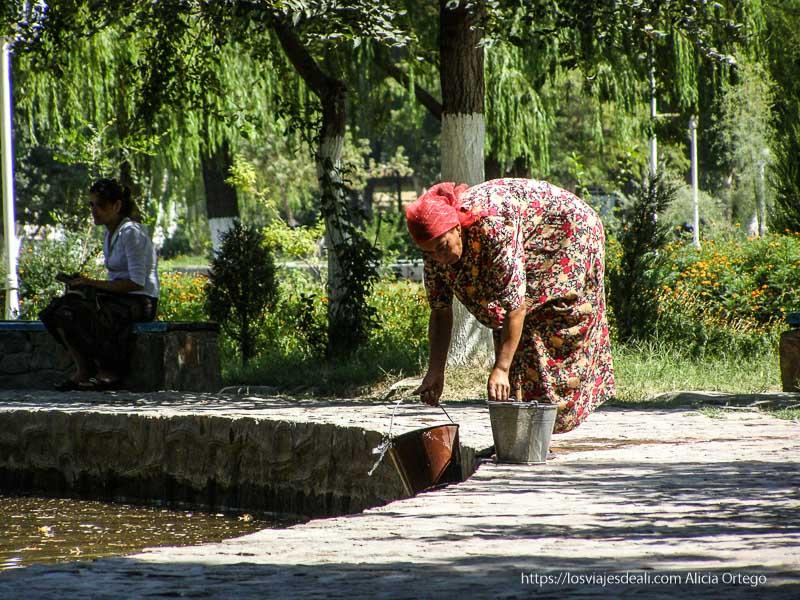 mujer con vestido floreado y pañuelo rojo en la cabeza llenando dos cubos de agua en un estanque en Fergana