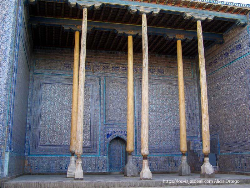 estancia de palacio de khiva abierta al patio con grandes columnas de madera y paredes y techos llenos de azulejos de colores azules