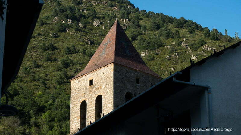 torre de la iglesia de bielsa con tejado puntiagudo y detrás montaña verde