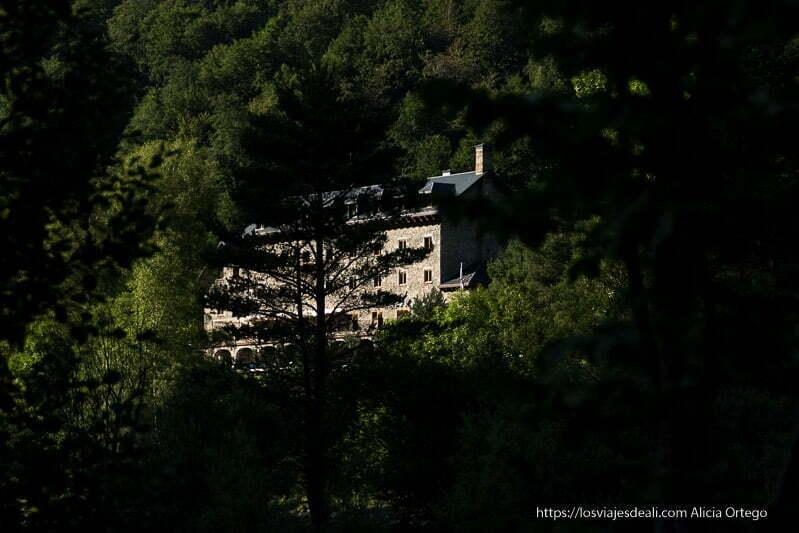 parador de bielsa en ladera de la montaña iluminado por el sol