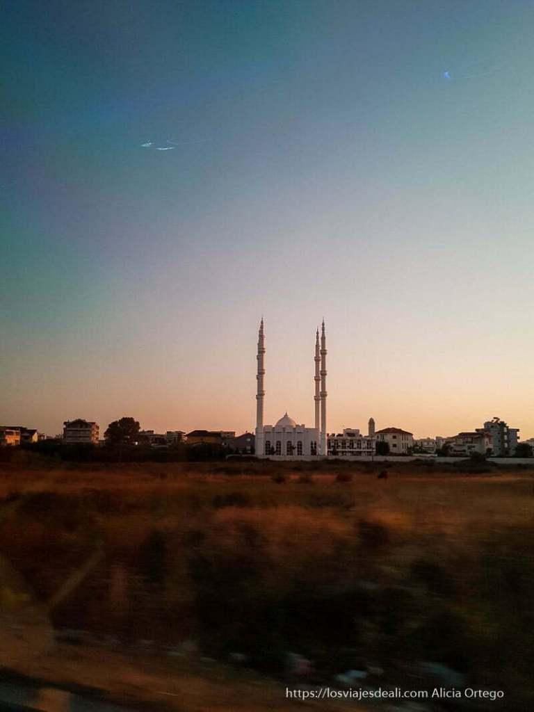 mezquita blanca con cuatro minaretes al atardecer desde la carretera en el viaje a Albania