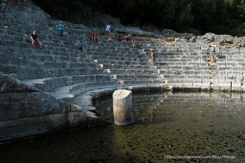 teatro antiguo con platea inundada donde se reflejan las gradas y restos de columna antigua en Butrinto