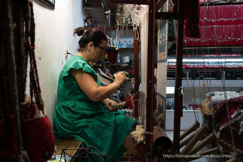 mujer del bazar con vestido verde trabajando en un telar