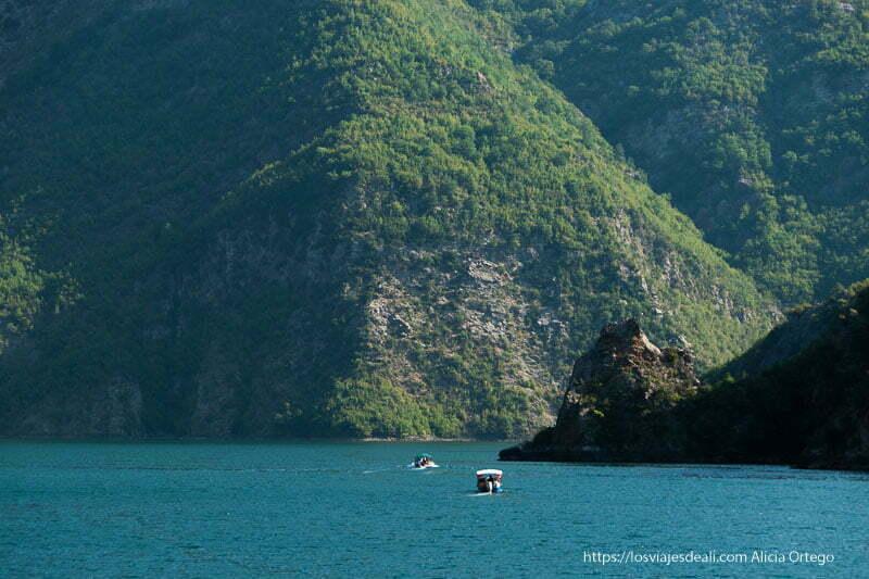 paisaje del lago Koman con grandes paredes cubiertas de bosque y agua azul