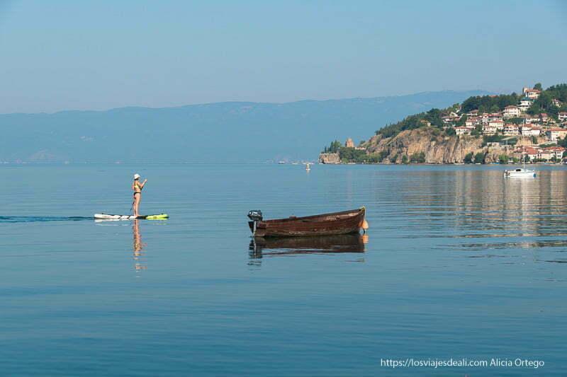 lago Ohrid de Macedonia con agua muy calmada, una barca de pesca y una mujer haciendo paddle surf