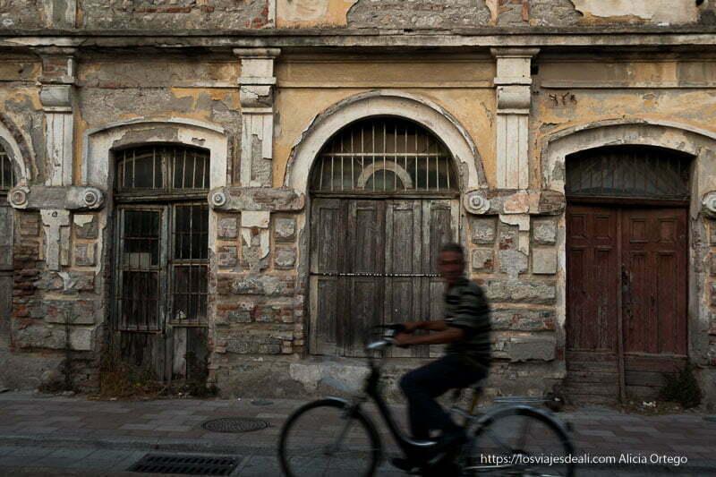 hombre circulando en bici desenfocado frente a fachada antigua de casa veneciana en el viaje a Albania