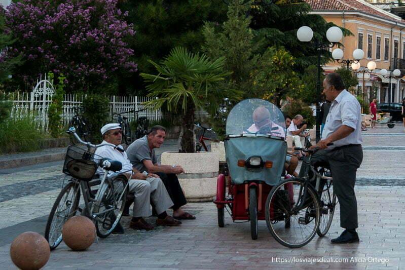 cuatro hombres sentados con sus bicis al lado en el centro de Shkoder