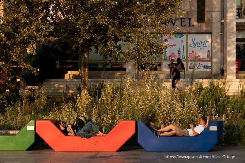 dos chicos tumbados en asientos de plástico de colores en el centro de Tirana