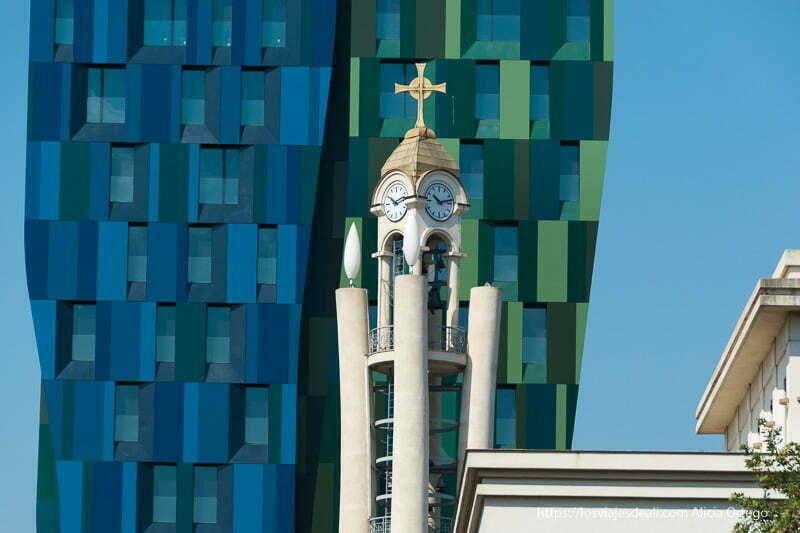 torre con dos relojes y una cruz ortodoxa contrastada con edificio nuevo moderno de color verde y azul en el viaje a Albania