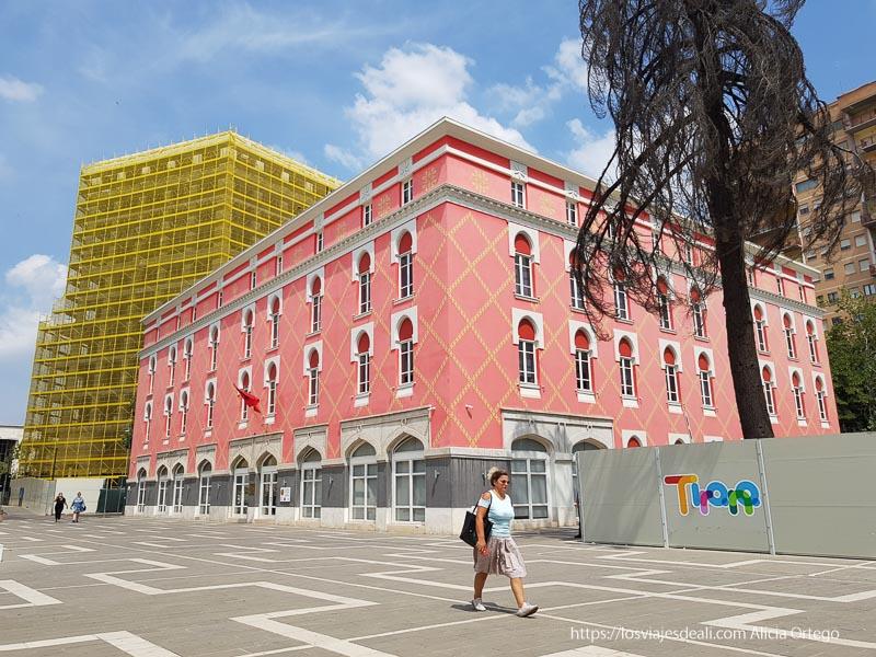 edificio pintado de color rosa con franjas amarillas en forma de rombo y detrás otro con andamios amarillos en Tirana, viaje a Albania