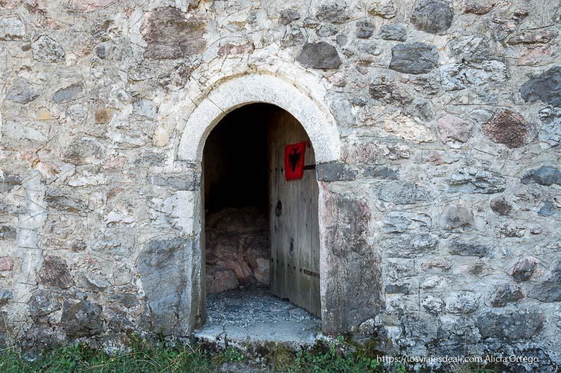 entrada a la kulla con un arco de piedra y puerta de madera
