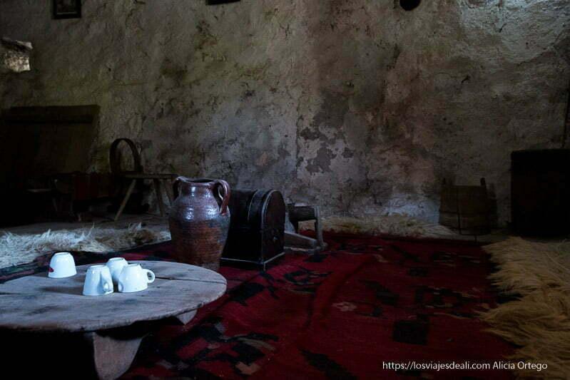 habitación de la kulla con tapiz de colores rojos, mesita baja con tazas, taburete de madera