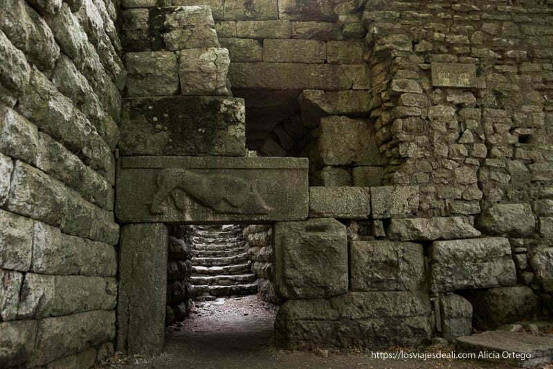 puerta con relieve en el dintel de una leona comiéndose un toro en la muralla