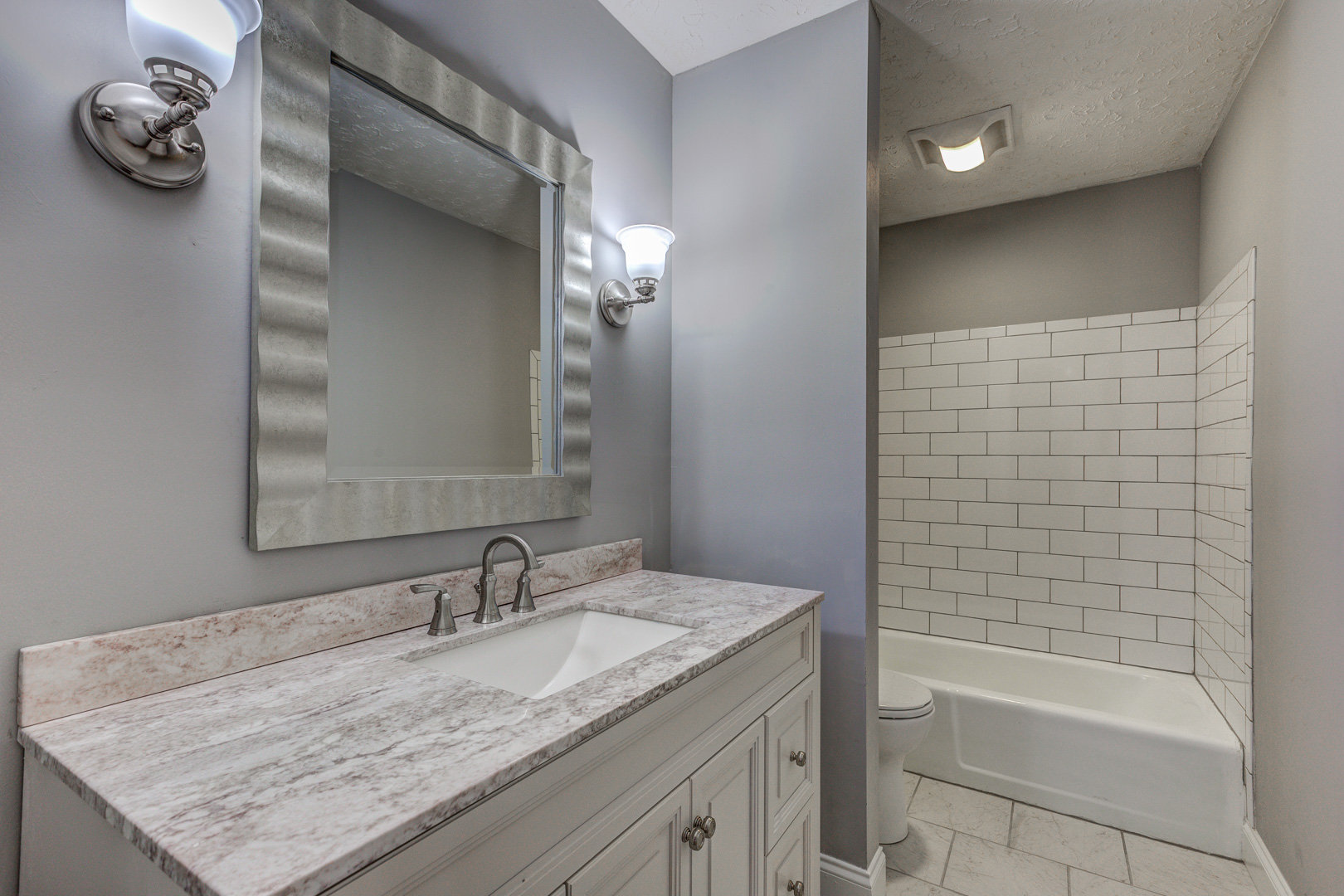 Bathroom remodel with granite countertops and subway tile shower