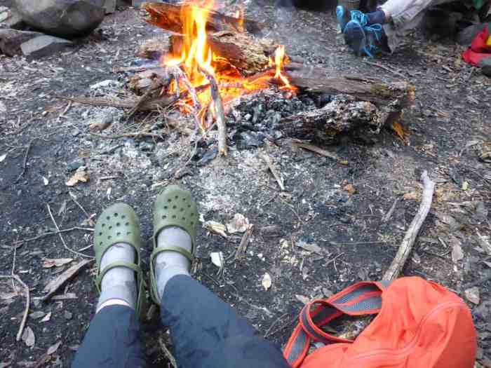 Relaxing by the fire, water and food in my orange foldable backpack.