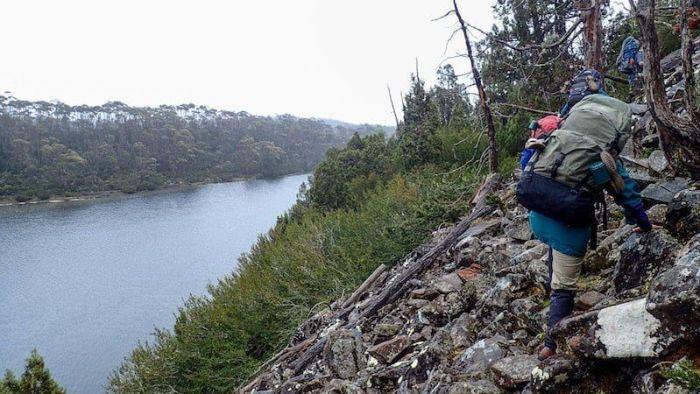 hiker on rocks traverses lake ball tasmania