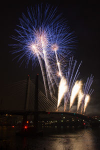 Blue and yellow fireworks exploding over Portland's Tilikum Crossing | LotsaSmiles Photography