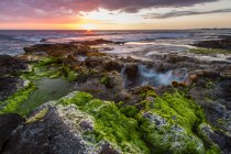 """The sun sets over a Hawaiian """"puka"""" - a water hole that spouts seawater - just south of Kona Airport."""