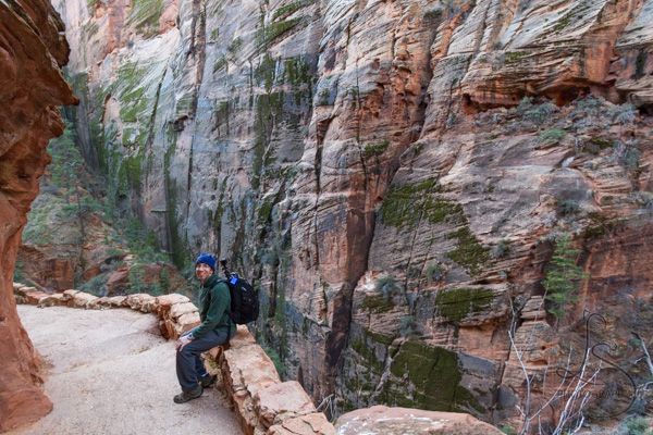 Man sitting on the edge of the Angels Landing trail with a mossy canyon wall behind him | LotsaSmiles Photography