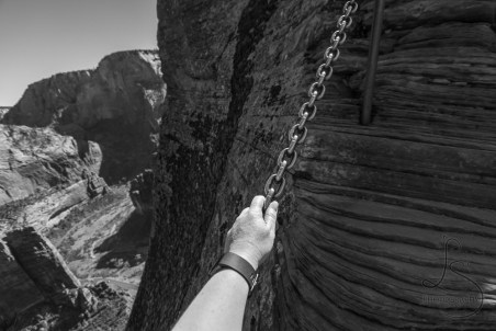 A hand gripping a chain in the rock face, with nothing but the Zion valley floor 2000 feet below the Angels Landing summit | LotsaSmiles Photography