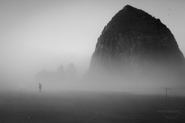 Silhouette of a man walking in front of a foggy Haystack Rock at Cannon Beach | LotsaSmiles Photography