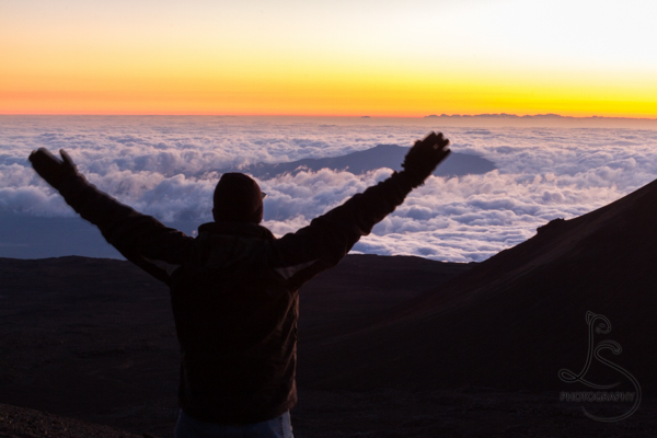 Silhouette of a man with hands overhead in front of a golden sunset over the clouds atop Mauna Kea | This Week On Instagram - LotsaSmiles Photography