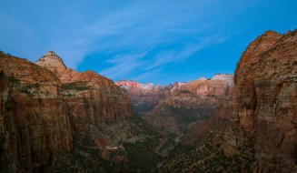 A car makes its way up the Zion valley just before dawn