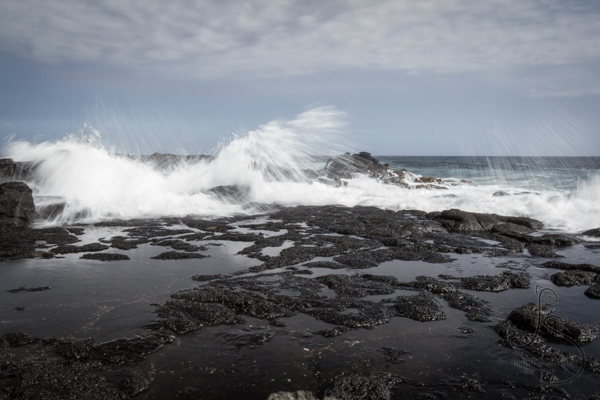 A wave crashing over a rocky Hawaiian beach | LotsaSmiles Photography