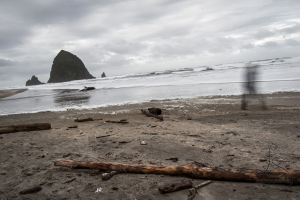Blurred figure walking along the beach in front of Cannon Beach's Haystack Rock | LotsaSmiles Photography