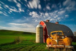 A rusty truck sits in front of a bright red barn in Washington's Palouse as clouds race overhead.