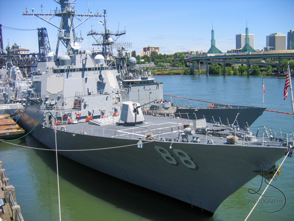 A navy ship moored in the Willamette River, with the Oregon Convention Center across the river | LotsaSmiles Photography