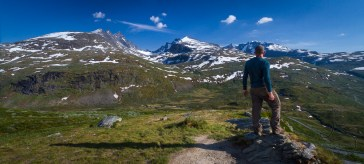 A man stands on the edge, overlooking the expansive Norwegian landscape