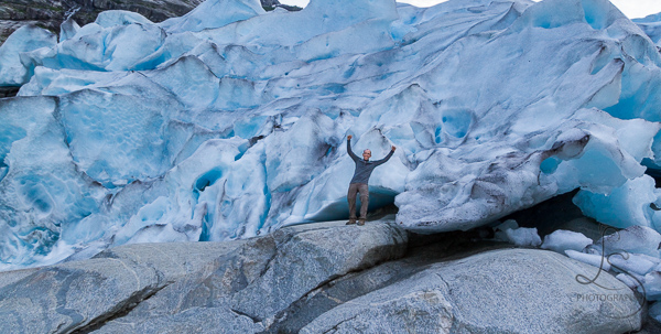 Aaron posing in front of the massive Nigardsbreen Glacier in Norway | LotsaSmiles Photography