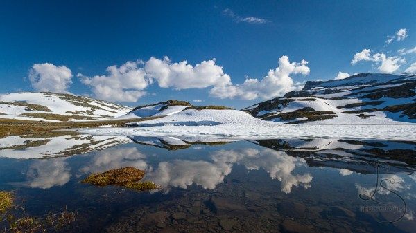 A snowy ridge and puffy clouds, perfectly reflected and a mirror-smooth lake in Norway | LotsaSmiles Photography