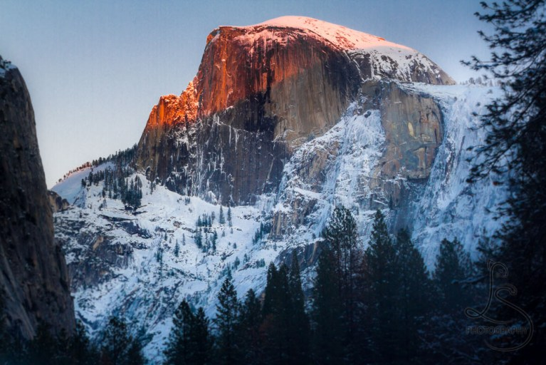 The sun sets in Yosemite National park, slipping off of the tip of Half Dome | LotsaSmiles Photography