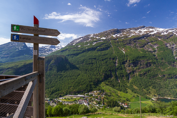 Trail signposts in front of a beautiful Norwegian vista in Geiranger | LotsaSmiles Photography