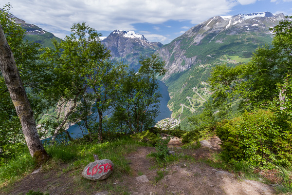 """The trail summit marker rock, painted with """"Losta,"""" with the Geiranger Fjord view beyond 